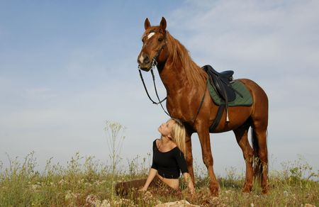 blond teenager and her brown horse in a field photo