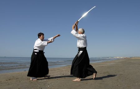 Two adults are training in Aikido on the beach photo