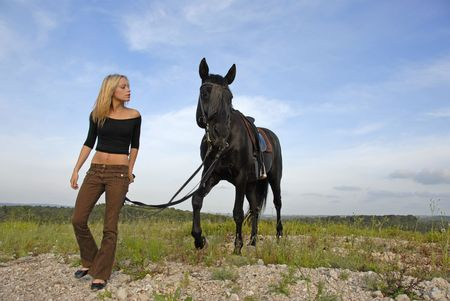 blond teenager and her black horsewalkin  in the nature photo