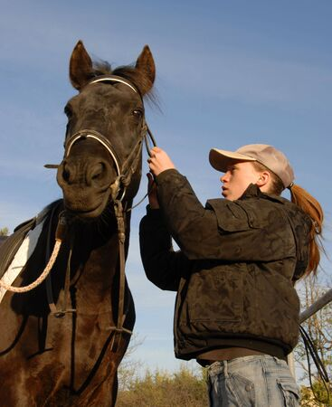 bridle: young teenager make a bridle to her black horse