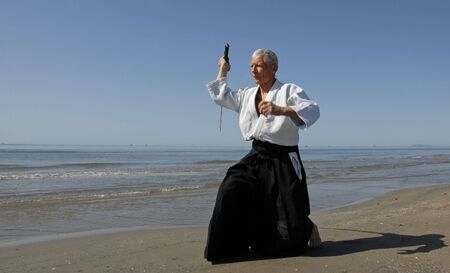 aikido: one old man are training in Aikido on the beach