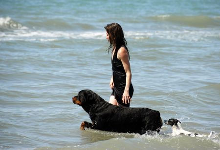 woman and her two dogs on the sea photo