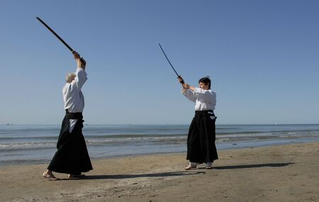 instruct: Two adults are training in Aikido on the beach