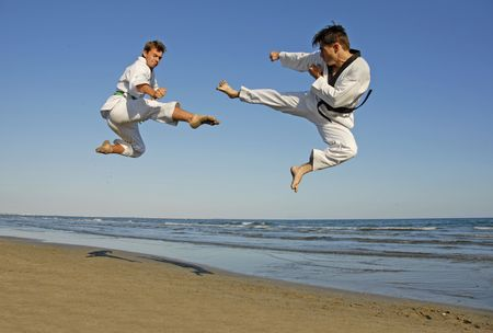 training of the two young men on the beach: taekwondo, martial sport