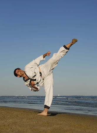 a young man is training in taekwondo on the beach