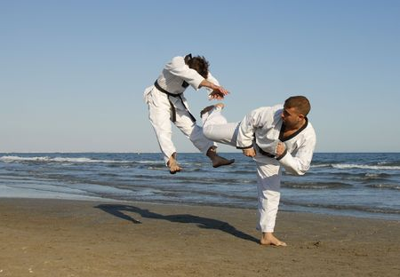 exercice: training of the two young men on the beach: taekwondo