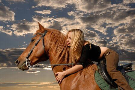 light brown horse: young riding girl in a storm sky with her brown stallion