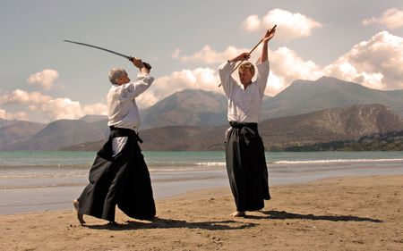 aikido: two adultes are training in aikido on a beach in japon