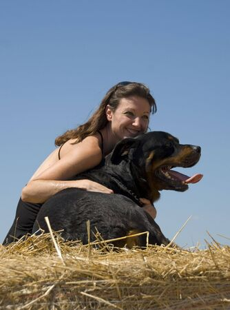 smiling young woman and her big black dog purebred rottweiler Stock Photo