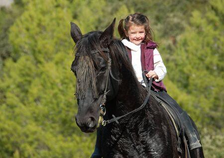 horseback: little smiling girl on her black stallion. focus on the child