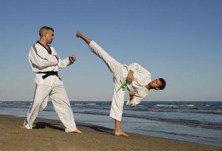 Deux hommes sont la formation en taekwondo sur la plage Banque d'images - 3979173