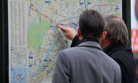itinerary: two men searching their itinerary in Paris, capital of France