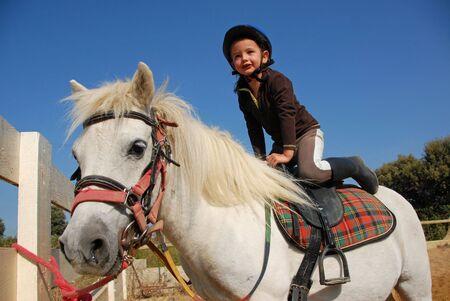 happy little girl and her friend white purebred shetland pony Stock Photo