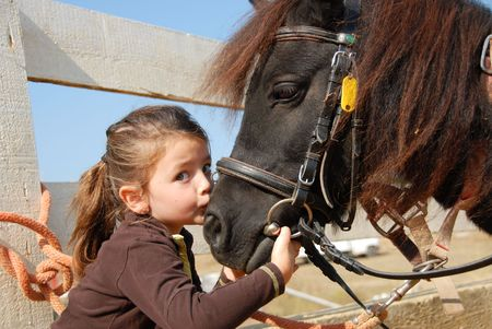 little girl kissing and her purebred shetland pony Stock Photo