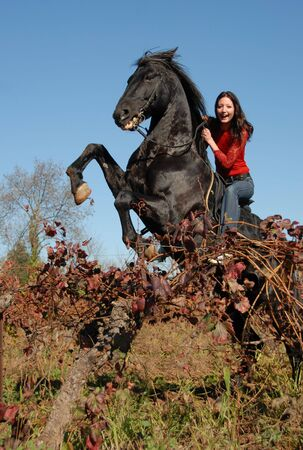 rearing black stallion and happy young girl in autumn Stock Photo
