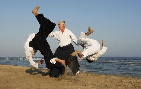 Three adults are training in Aikido on the beach Stock Photo