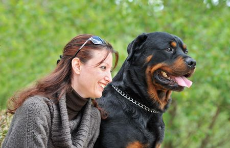 beautiful smiling young woman and her purebred rottweiler Stock Photo