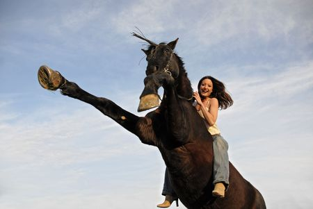 rearing black stallion and laughing girl in a blue sky. focus on the woman. photo