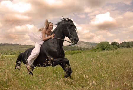 galloping beautiful wedding woman on her black stallion