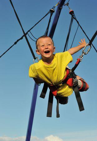 ni�o saltando: Ni�o peque�o salto en la cama el�stica (bungee jumping). Foto de archivo