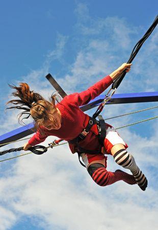 bungee jumping: joven adolescente de saltar sobre la cama elástica (bungee jumping). Foto de archivo