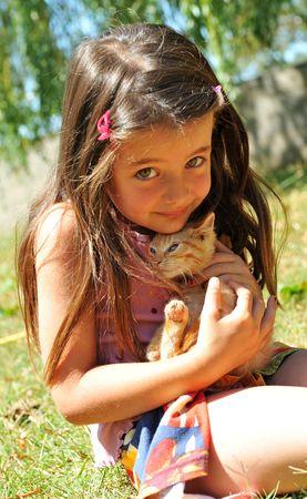 niñas sonriendo: niña y gato en un jardín