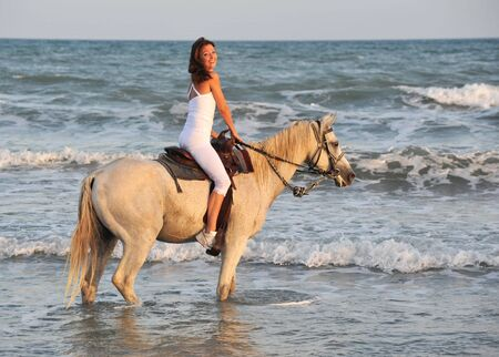 horse laugh: smiling riding young woman in the sea Stock Photo
