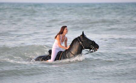 Schwimmen winth junge Frau ihren schwarzen Hengst im Meer