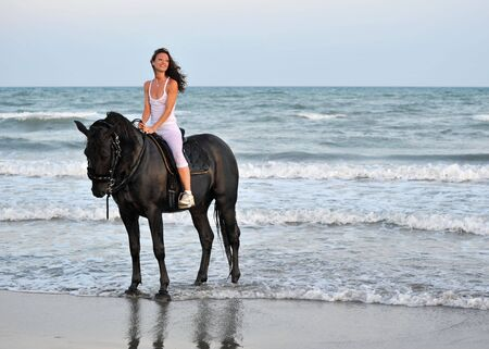 horseback riding: young woman an her black stallion in the sea
