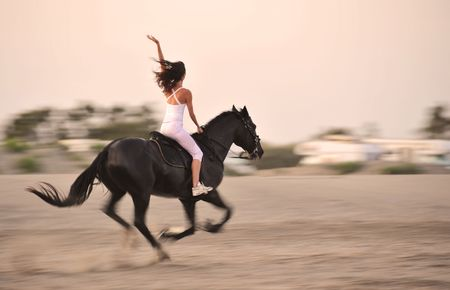 horse riding: galloping black stallion with a young girl on a beach
