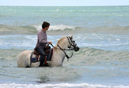 riding man and his white horse in the sea photo