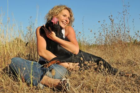 young smiling woman and herdog: purebred beauceron in a fiedl photo
