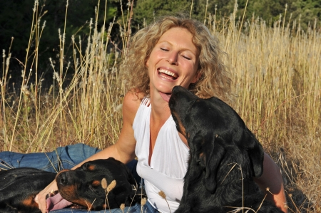 laughing young woman and her two dogs: rottweiler and french shepherd photo