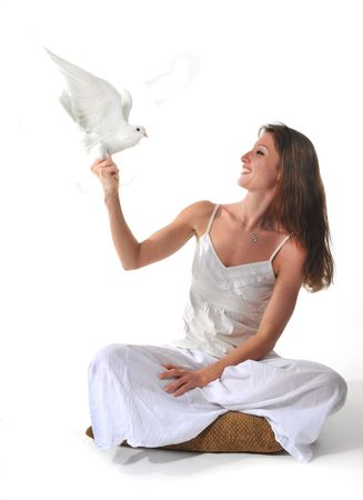young smiling woman and her white dove in a studio photo