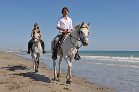 father and daughter are riding with their white horses on the beach photo