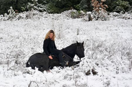 blond girl and her black stallion laid down in the snow photo