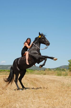 young smiling woman on her black rearing stallion in a field photo