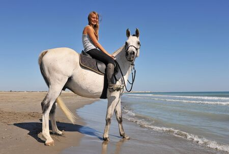 smiling riding teenager and her white horse on the beach photo