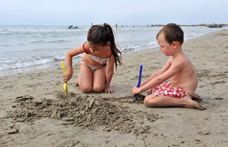 young children are playing on the beach photo