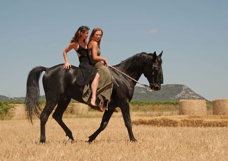 horse laugh: two beautiful young women horseback riding on a black stallion