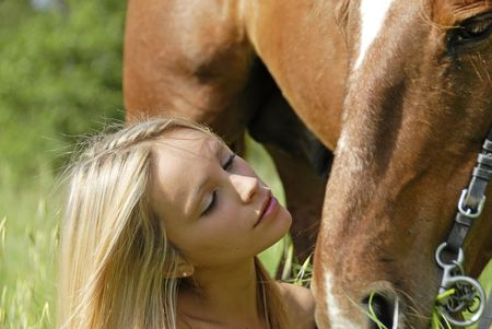 horse blonde: young blond teenager and her brown stallion in a field Stock Photo