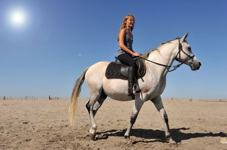 young teen and her white horse on the beach, sun with halo in the sky Stock Photo