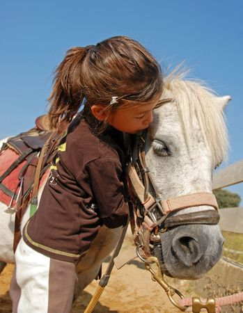 little girl kissing her best friend shetland pony