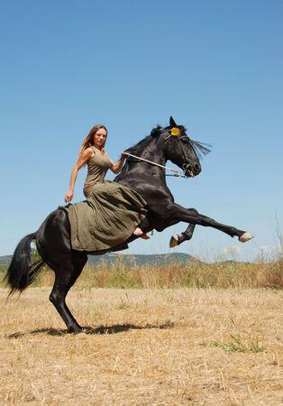 caballo negro: mujer joven y su cr�a semental en un campo en primavera