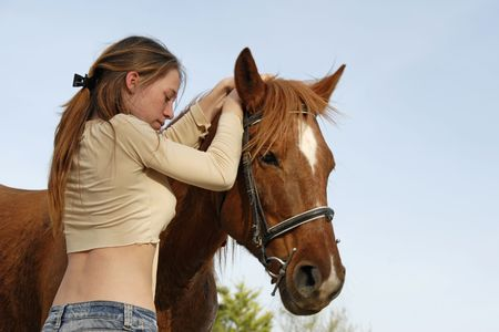 beautiful teenager and her brown horse outdoors photo