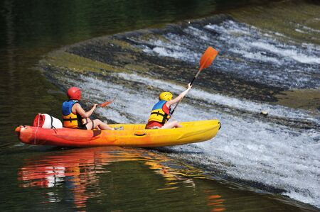 two young adults kayaking on the herault river