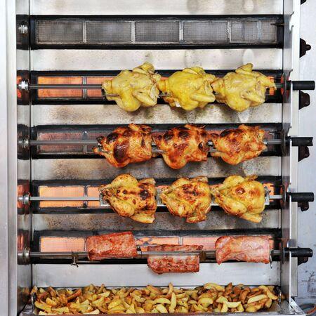 pollo rostizado: Todo pollos y carne de cerdo sobre rotisserie escupir y patatoes en un mercado
