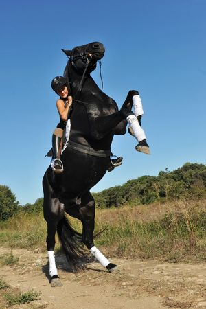 young woman and her beautiful black stallion rearing up photo