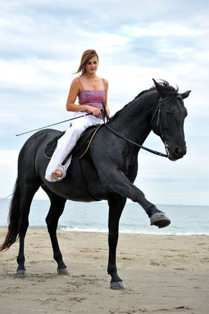 beautiful black stallion on the beach with young woman