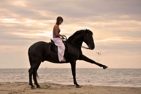 mujer en caballo: hermoso semental negro en la playa con joven  Foto de archivo